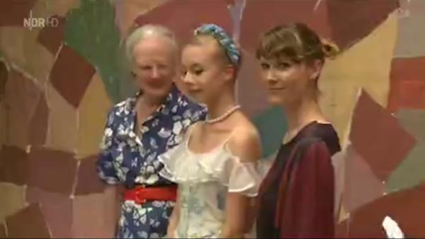 Dronning Margrethe II og komponisten OH Land omkranser en av Pantomitetrets ballettsolister fra Askepot. Foto fra EuroNews - Tivoli.