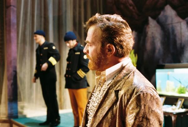Luca Titolo synger glimrende som Don Alfonso en stor musikalsk opplevelse, Hans elegante jakke, som så ut til å kunne vøre i slangeskinn er elegant, men en så flott gentleman kunne ha fått et noblere kostymeskift underveis, dette ble for primitivt. Her med Guglielmo og Ferrando i uniformer bak seg.