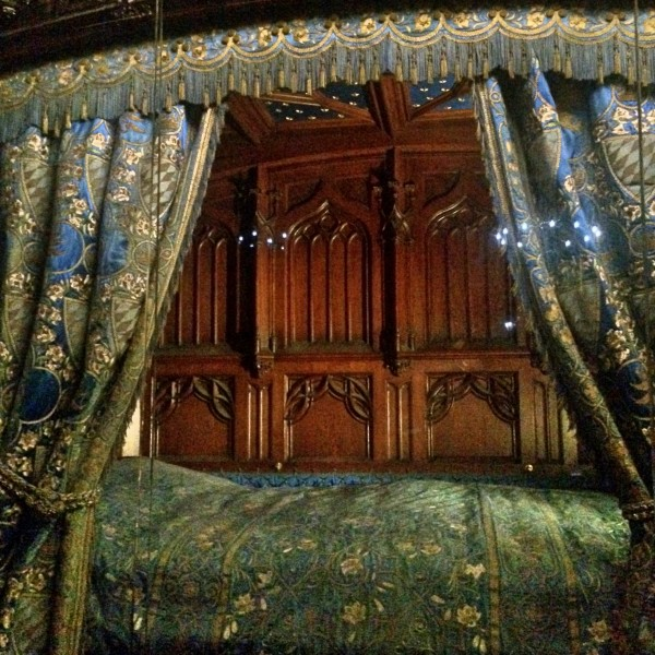 """Ludwig II bed. Contrasting th either rooms, the Bedroom is sumptuously carved in Neo Gothis style. It is said that 14 woodcarvers have worked 4 1/2 year to create the room. The bed is covered with richly embroidered draperies. The wall paintings illustrate the """"Tristan and Isolde"""" story."""